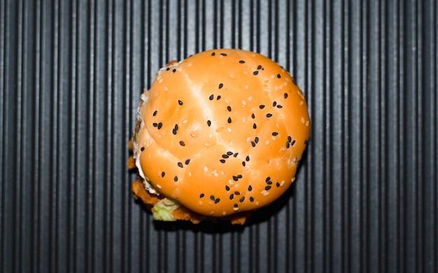 Burger na grillu elektrycznym, wewnątrz. opiekana bułka z sezamem, widok z góry. gotowanie fast foodów w kuchni.