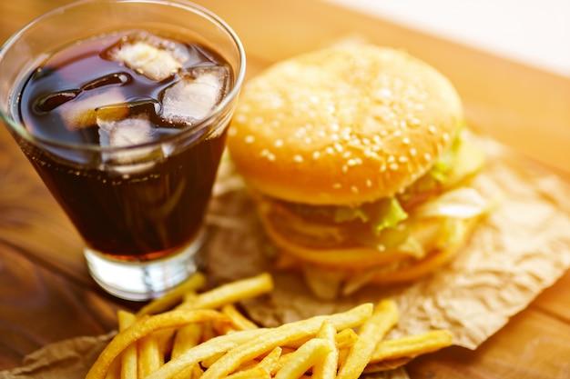Burger na papierze rzemieślniczym z frytkami i napojami gazowanymi