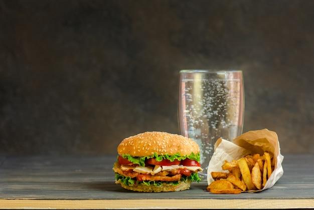 Burger na rustykalnej desce i arbonowany słodki napój w szklance