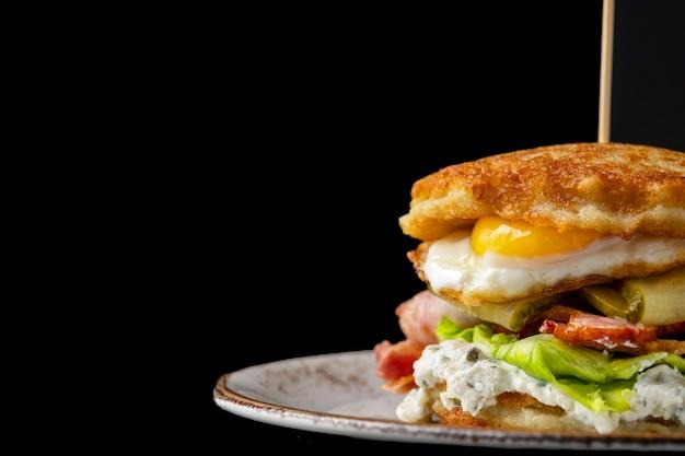 Burger placki ziemniaczane z jajkiem sadzonym, bekonem i ogórkiem na czarnym tle.