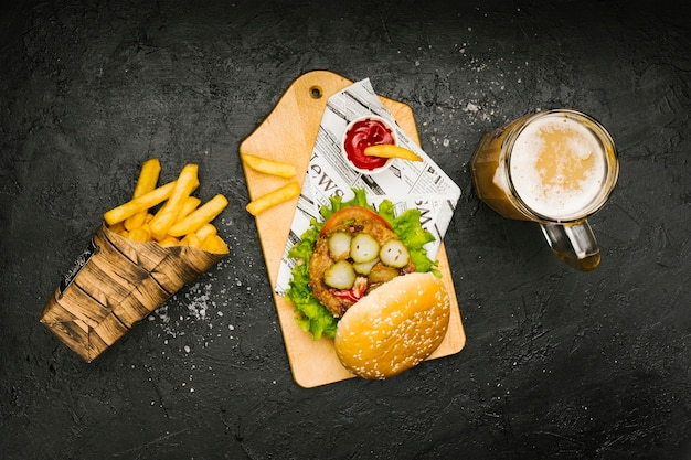 Burger płaski na desce z frytkami i piwem