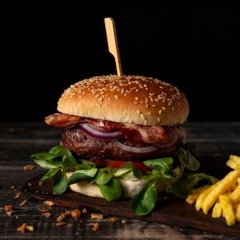 Burger pod dużym kątem z frytkami na stole