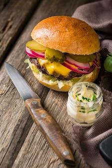 Burger pod dużym kątem z piklami i nożem