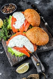 Burger rybny z solonym łososiem, awokado, sosem musztardowym, ogórkiem i sałatką lodową. widok z góry.
