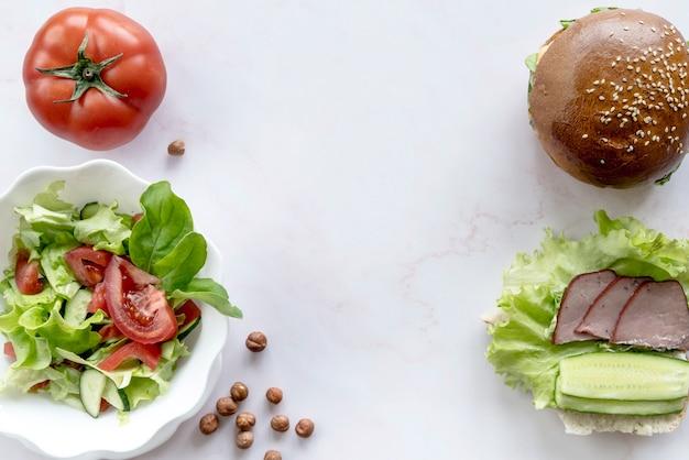 Burger; sałatka warzywna; cały pomidor; orzech laskowy na białej powierzchni