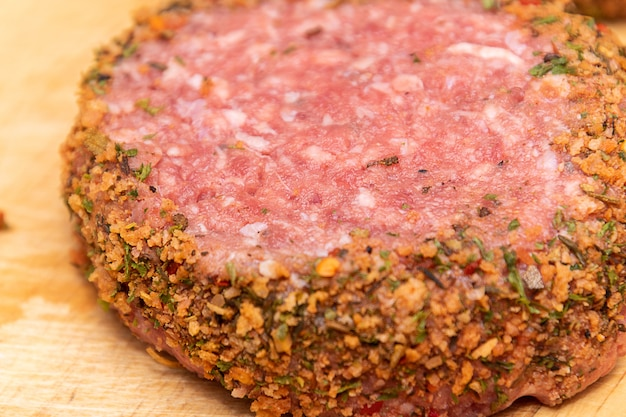 Burger świeży surowy jagnięcina na drewnianej desce do krojenia.