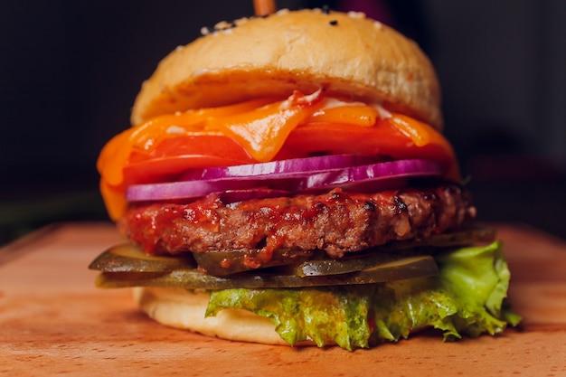 Burger ułożony w stosy ze świeżymi dodatkami na bułce rzemieślniczej z pełnego ziarna