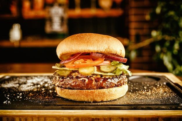 Burger w barze z serem, boczkiem i cebulą.