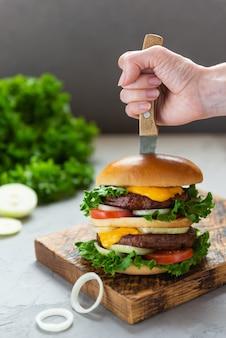 Burger wegański z nożem w ręku na drewnianej desce
