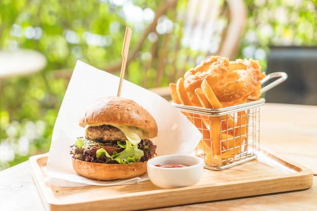 Burger wieprzowy z krążkami cebuli i frytkami