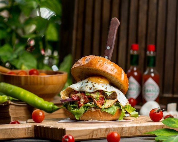 Burger wołowy z pomidorami i sałatą jajeczną i cebulą