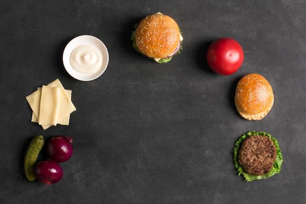 Burger wołowy z sałatą i sosem na czarnej tablicy