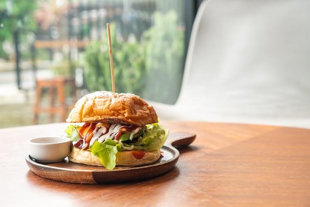 Burger wołowy z serem i sosem na drewnianym talerzu