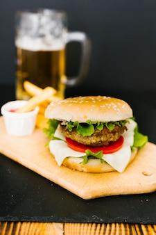 Burger z bliska z dużym frytkami na talerzu
