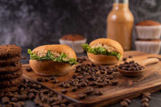 Burger z drewnianą deską do krojenia, w tym babeczki i ziarna kawy.