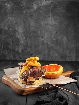 Burger z duszonym żebrem wołowym i sosem serowym na ciemnym tle