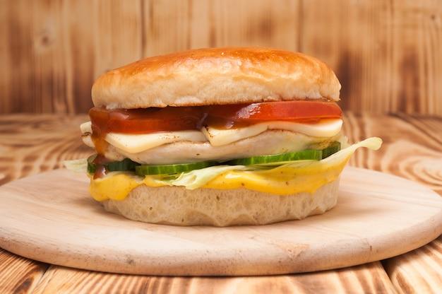 Burger z filetem z kurczaka, serem, pomidorami, ogórkami i pomidorami