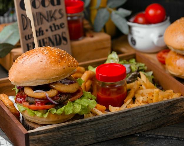 Burger z frytkami i sosem pomidorowym.