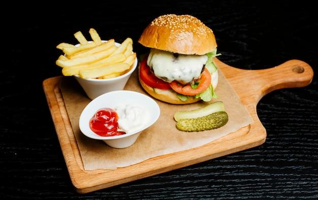Burger z frytkami, ogórkami i sosem do smażenia