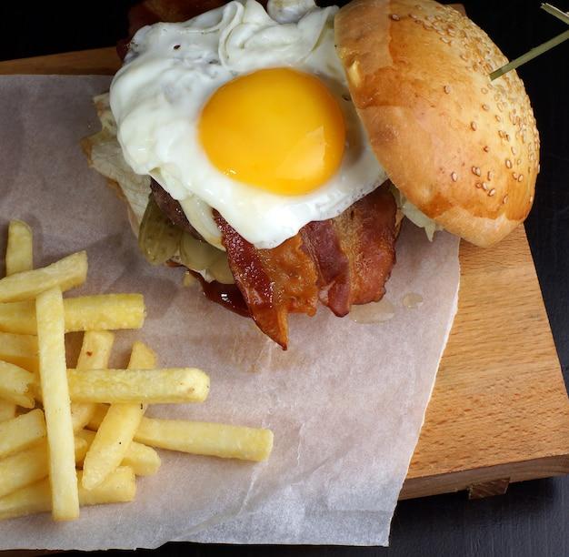 Burger z jajkiem na śniadanie i frytkami.