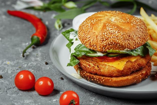Burger z kurczaka z frytkami i surówką na starym betonowym stole