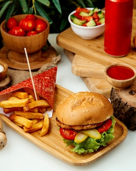 Burger z kurczaka z frytkami na stole