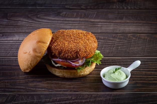 Burger z kurczaka z sałatą, pomidorem, fioletową cebulą i ręcznie robionym majonezem na drewnianym stole. pyszne.