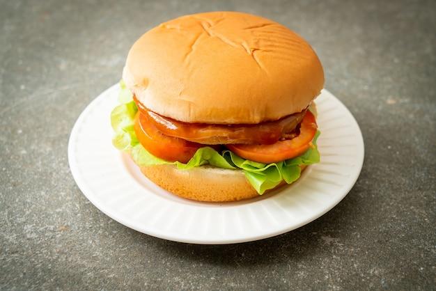 Burger z kurczaka z sosem na białym talerzu