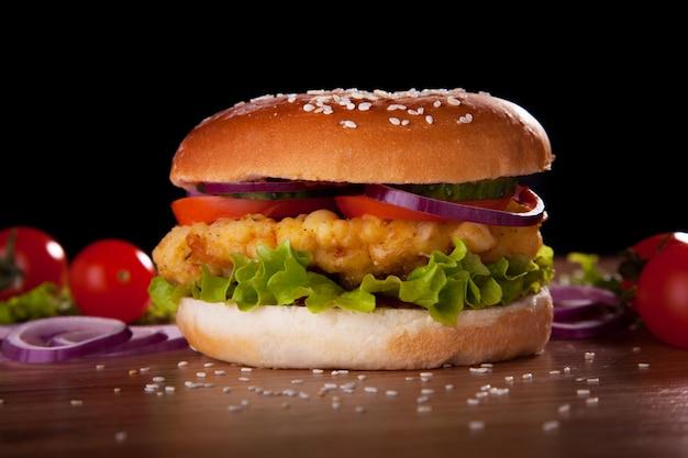 Burger z kurczakiem, sałatką, ogórkami, pomidorami i cebulą na czarnym tle.