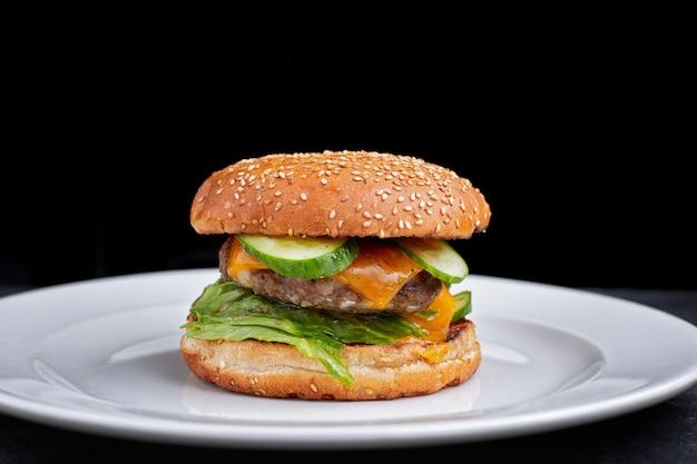Burger z mięsem, serem. ogórek i sałata na białym talerzu na czarnym tle
