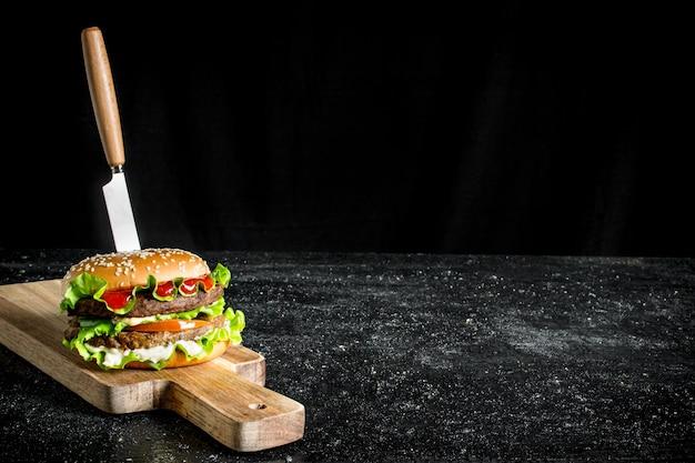 Burger z nożem. na czarnym tle rustykalnym