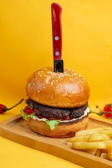 Burger z nożem w środku i frytkami