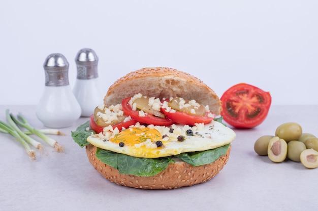 Burger z omletem, pomidorami, pieczarkami i cebulą na białej powierzchni.