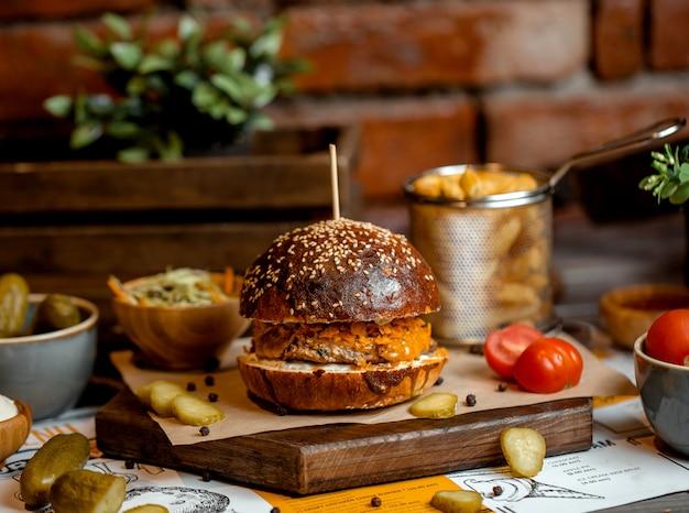 Burger z pasztecikiem z kurczaka podawany z frytkami, sałatką coleslaw i marynatami