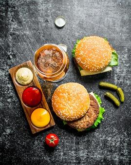 Burger z piwem, sosami i korniszonami. na czarnym tle rustykalnym