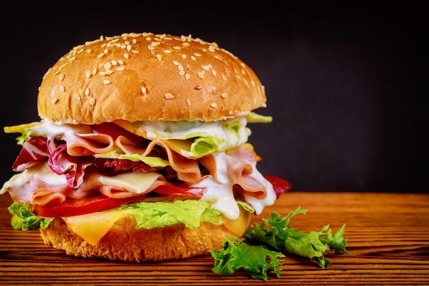 Burger z sałatą, serem, szynką i pomidorem na ciemnej powierzchni