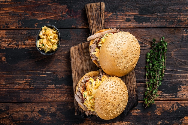Burger z szarpaną wieprzowiną z sosem bbq i sałatką coleslaw. ciemne drewniane tło. widok z góry.