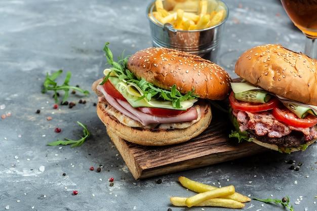 Burger z szynką, serem, boczkiem, surówką i warzywami. duży burger, amerykańskie fast foody. baner, menu, miejsce na przepis na tekst
