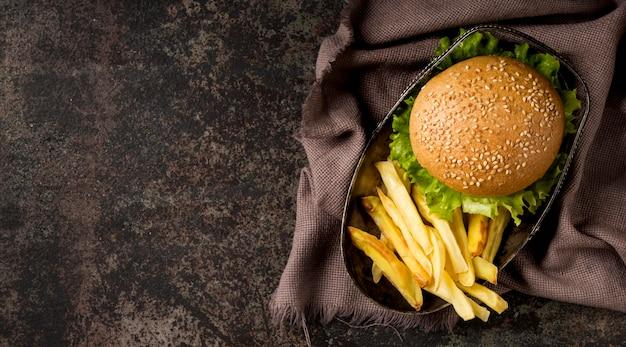 Burger z widokiem z góry i frytki z ręcznikiem kuchennym