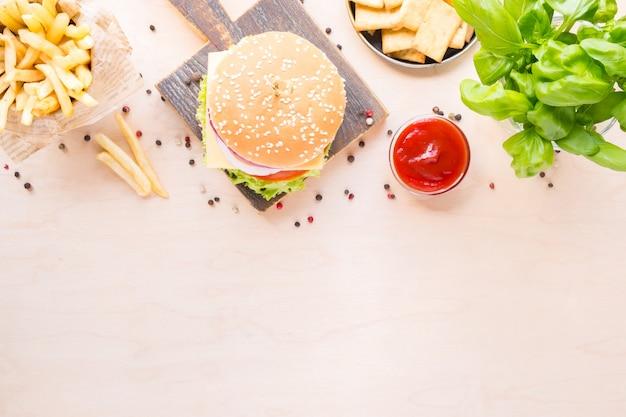 Burger z widokiem z góry z sosem i frytkami na drewnianym
