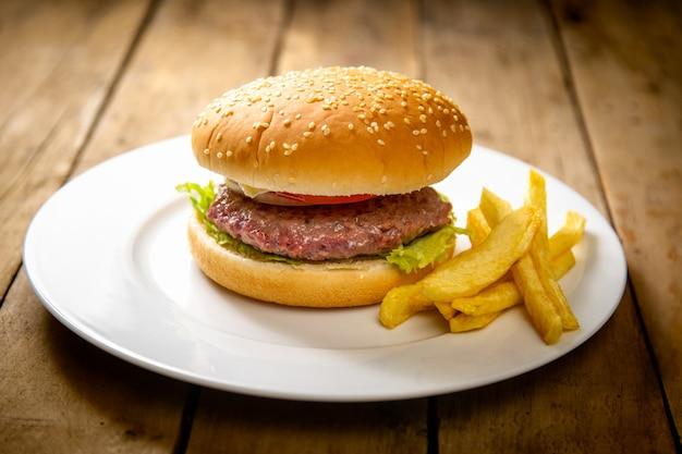 Burger z ziemniakami na białym talerzu na drewnianym stole