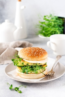 Burger zdrowy wegetariański z pędami jajka i grochu i nasionami microgreen, świeża sałatka, plasterek ogórka na desce do krojenia na jasnym tle. selektywne skupienie