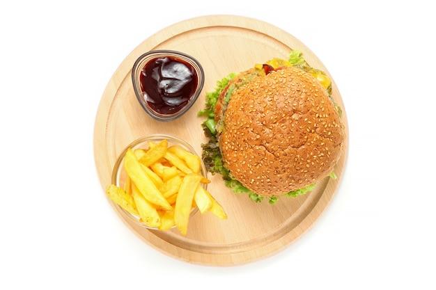 Burger ze smażonym ziemniakiem i sosem na drewnianym stoisku z desek
