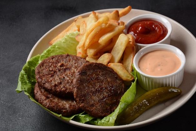 Burgerowe steki mięsne frytki i sałatka na czarnym tle