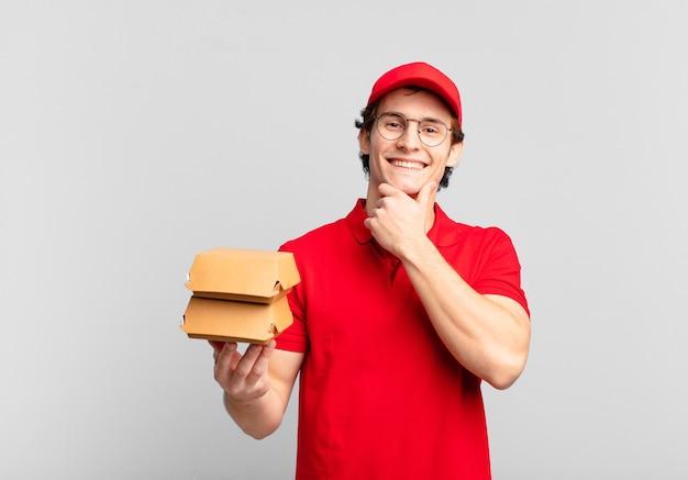 Burgery dostarczają chłopakowi uśmiechniętemu z radosnym, pewnym siebie wyrazem twarzy z ręką na brodzie, zastanawiając się i patrząc w bok