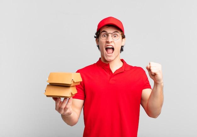 Burgery dostarczają chłopcu krzyczącego agresywnie z gniewnym wyrazem twarzy lub z zaciśniętymi pięściami, świętując sukces