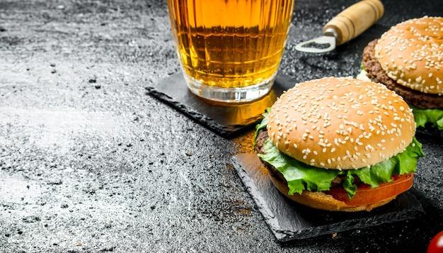 Burgery i piwo w szklance. na czarnym tle rustykalnym