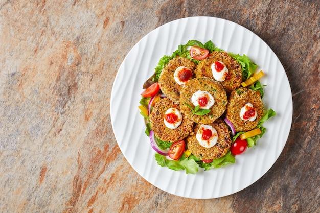 Burgery wegańskie, paszteciki z roślin strączkowych, cebuli i zieleniny w panierce z bułki tartej panko podane na białym talerzu ze świeżą sałatą i sosem pomidorowym, widok poziomy z góry, płasko leżący, wolna przestrzeń