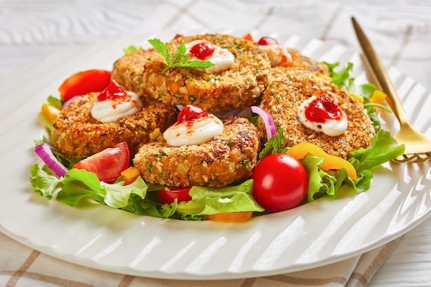 Burgery wegetariańskie, paszteciki z roślin strączkowych, cebuli i zieleni podawane na białym talerzu ze świeżą sałatą i sosem pomidorowym, widok poziomy z góry