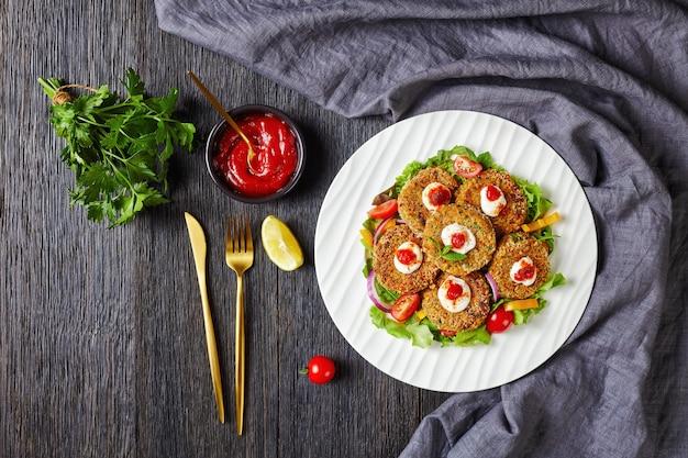 Burgery wegetariańskie, paszteciki z roślin strączkowych, cebuli i zieleniny w panierce z bułki tartej panko podane na białym talerzu ze świeżą sałatą i sosem pomidorowym, widok poziomy z góry, płasko leżący, wolna przestrzeń
